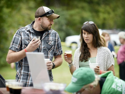 Casey Grzybowski and Nikole Camacho, both of Mt. Gretna, sample a beer from the Mt. Gretna Craft Brewery Sunday during the Inaugural Sip & Stroll event at the Quittie Creek Nature Park. The event featured wine, beer and food samples and jazz music.