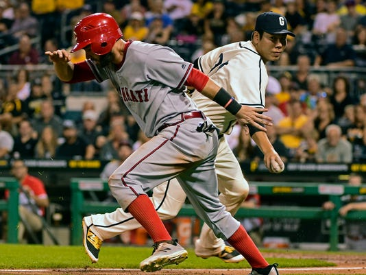 Cincinnati Reds' Jose Peraza, left, tries to get away from the tag of Pittsburgh Pirates' Jung Ho Kang in the seventh inning of a baseball game in Pittsburgh, Friday, Sept. 9, 2016. Peraza was called out to end the inning. (AP Photo/Fred Vuich)