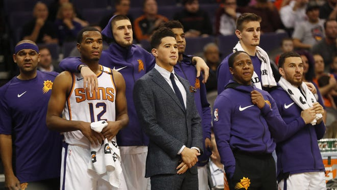 Phoenix Suns guard Devin Booker (center) and his teammates watch the final minutes against the Toronto Raptors during the fourth quarter at Talking Stick Resort Arena in Phoenix, Ariz. December 13, 2017.