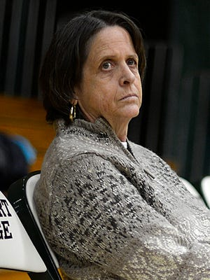 St. Norbert College women's basketball head coach Connie Tilley sits on the bench as she watches her players warm up.