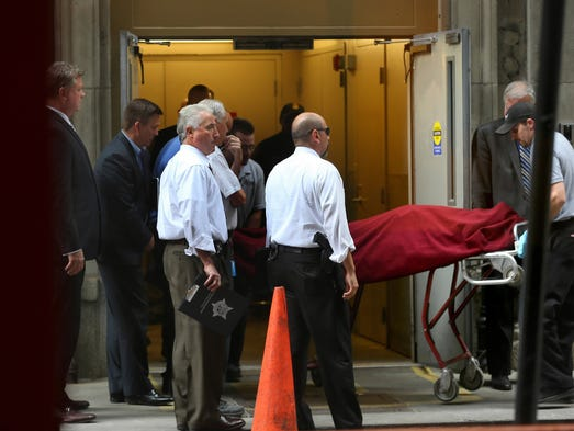 The body of the alleged shooter is taken out a side door after police investigated the crime scene at the Bank of American building Thursday, July 31, 2014, in downtown Chicago. A man, who allegedly had been demoted in his job, shot the CEO of his company and then killed himself in the Bank of America building on South LaSalle Street. The CEO of the company is in critical condition after reports that he was shot in the head and abdomen.