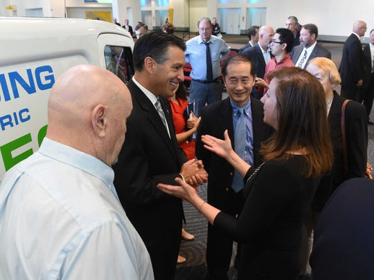 Gov. Brian Sandoval chats with Cenntro Automotive Executive Vice President Marianne McInerney after a press conference Friday announcing Cenntro's move to Sparks. In the center is Cenntro's Founder Peter Wang. At left is Sparks Mayor Geno Martini.