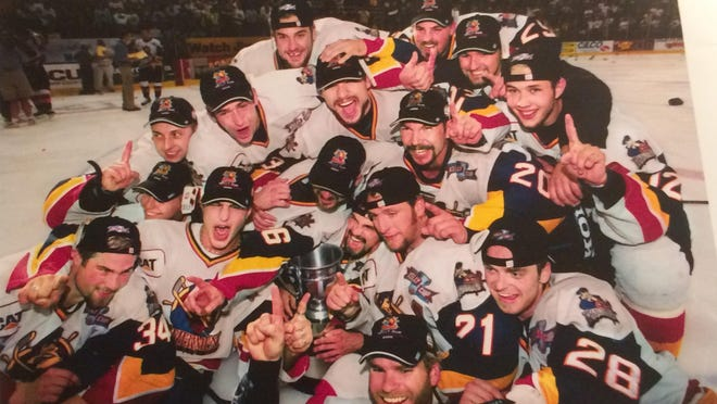 Peoria Rivermen celebrate with the Kelly Cup as champions after clinching in Carver Arena in 1999-2000. Darren Clark (28) is at the bottom right corner.