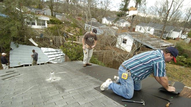 Roofers work on a storm-damaged home in the Hickory Hill neighborhood in Thomson, Ga., in this 2007 file image.