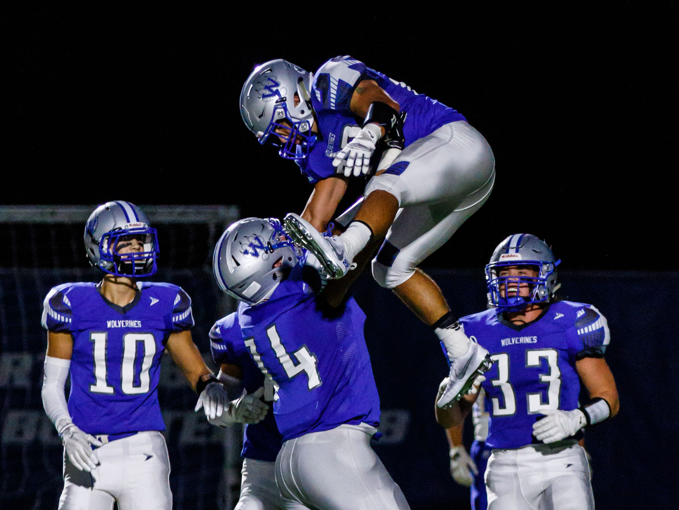Waukesha West lineman Bryce Texeira (74) hoists teammate