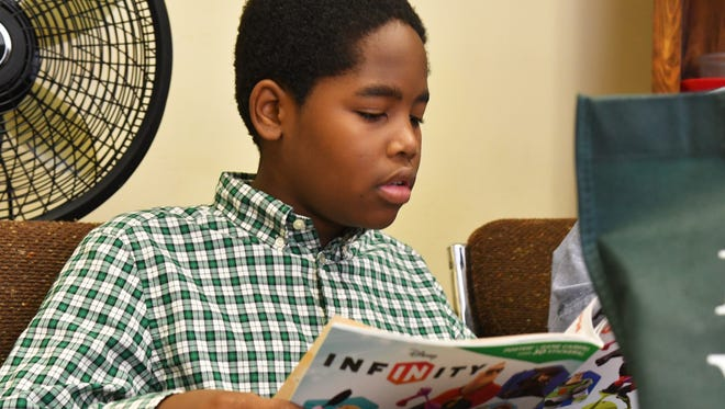 Erique Ray, 11, checks out some of the books available. The Community Read & Feed Program sets up at three locations, including Florida Avenue Church of Christ in Palm Bay at the border of Melbourne. Volunteers serve top meals to go, and a reading program for youth in the neighborhood.