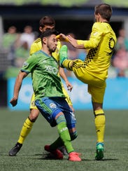 Columbus Crew midfielder Pedro Santos, right, makes