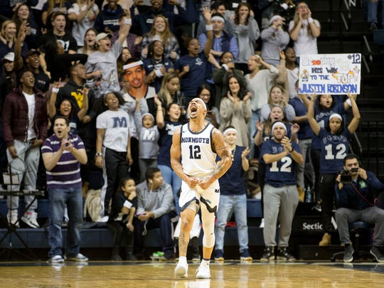 Monmouth's Justin Robinson celebrates after the game for being the top scorer in Monmouth University history.  Saint Peter's at Monmouth University basketball. 