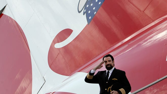 Actor John Travolta salutes from air stairs positioned next to a Qantas A380 at Dallas/Fort Worth Airport on Sept. 29, 2014. Travolta, Qantas' Good Will Ambassador, was on hand as the airline celebrated its inaugural A380 flight to the airport.