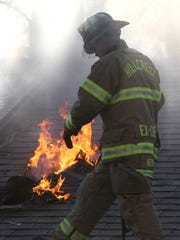 Firefighters work on the roof during a house fire on