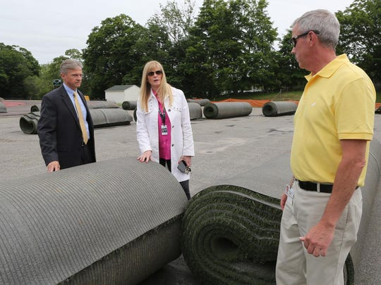 From left, Pleasantville school's Assistant Superintendent David Quattrocchi, Superintendent Mary Fox-Alter and Director of Facilities Steve Chamberlain. The group stands on the Pleasantville High School's track with rolls of synthetic turf that is being removed and replaced with synthetic turf with organic infill.