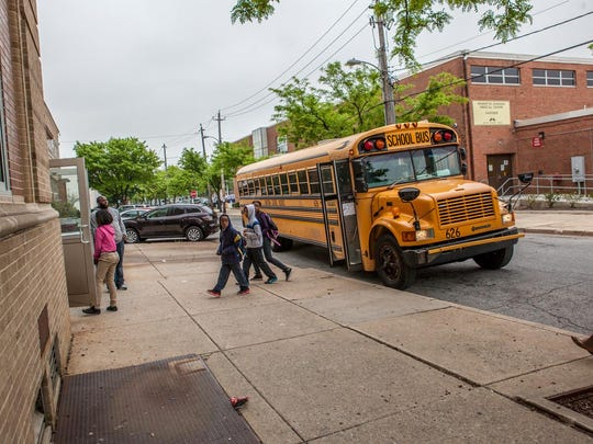 Students walk from a bus into Bancroft Elementary School.