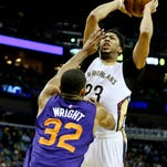 Pelicans forward Anthony Davis shoots over the Suns' Brandan Wright during the first quarter Friday at the Smoothie King Center. Davis later left the game after getting struck in the throat, but he returned.