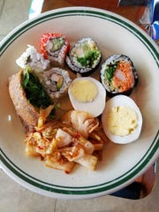 This lunch, including vegetable sushi, kimchi, and