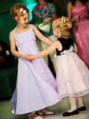 Emma Stumpf (left), then 8 and a second-grader at Whiteland Elementary School, danced with her sister Elyssa, then 2. They and a third sister, Ellie, 7, participated in Riley Hospital for Children at IU Health's first prom for its cancer patients on May 7, 2010.
