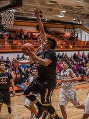 Navajo Prep's Tyler Pete attacks the basket against Aztec on Saturday at Lillywhite Gym.