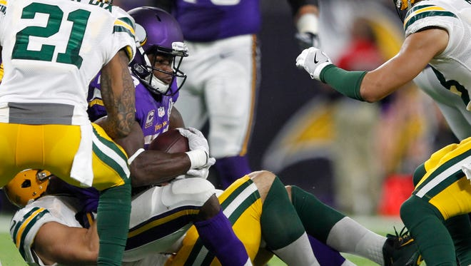 Minnesota Vikings running back Adrian Peterson, center, is tackled by Green Bay Packers outside linebacker Kyler Fackrell, left, during the second half of an NFL football game Sunday, Sept. 18, 2016, in Minneapolis. Peterson was injured on the play and was helped off the field. (AP Photo/Andy Clayton-King)