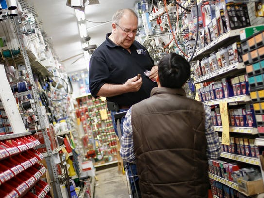 Okemos Ace Hardware owner Jim Raynak helps a customer