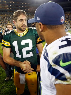 Green Bay Packers' Aaron Rodgers shakes hands with Seattle Seahawks' Russell Wilson during the second half of an NFL football game Sunday, Sept. 20, 2015, in Green Bay, Wis. The Packers won 27-17.