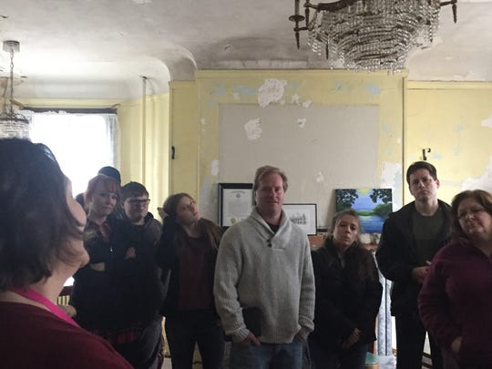A tour group listens to Friends of White Hill Mansion guide Loretta Kelly, left, during a tour about the history - and ghosts - of the house that the Friends are trying to restore.