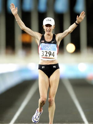 Deena Kastor of the United States crosses the finish line to win the bronze medal in the women's marathon at the 2004 Olympic Games in Athens, Greece.