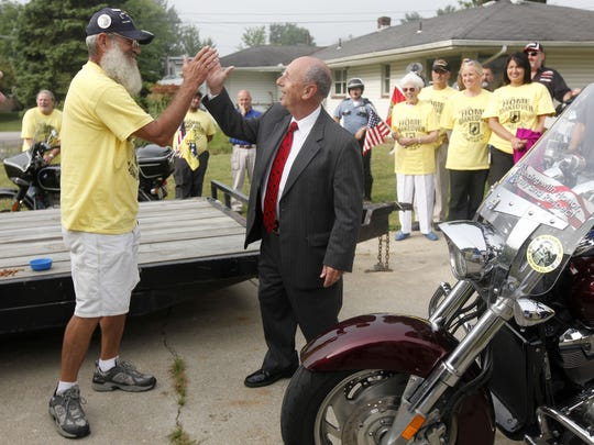 Keith Maupin gives a high five to Ed Hartman, spokesman