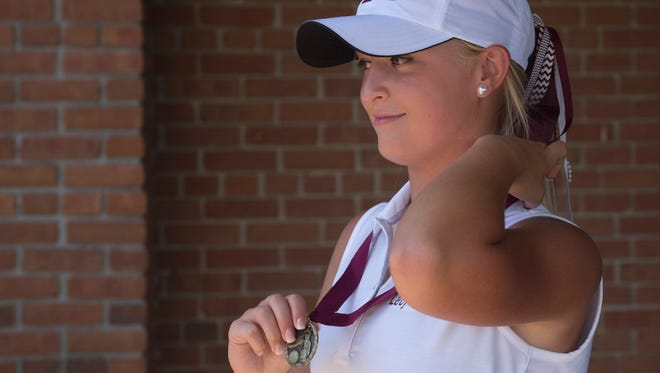 Henderson County's Payton Carter adjusts her medal after winning the individual title for the Henderson County Invitational at the Henderson County Country Club July 31, 2017.