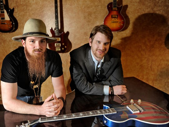 From left, Nashville country artist Tim Montana and Gibson Guitar's , Alex Juszkiewicz with the American Sniper guitar March 27, 2015, in Nashville in Tenn.