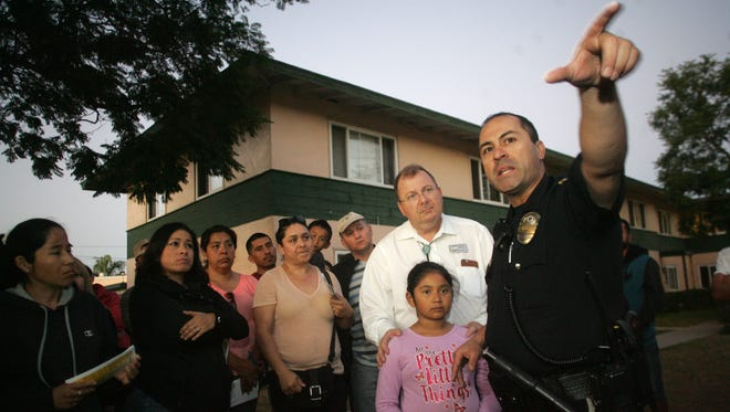 Oxnard Police officer Manual Perez answers a question from apartment residents on how they can help with the traffic issues in front of the apartment complex.
