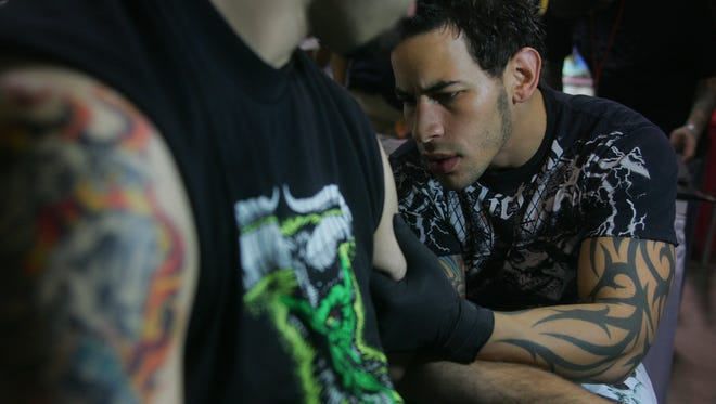 2007 archive photo of tattoo artist Christian Masot, of Silk City Tattoo in Hawthorne as he makes a tattoo of Rita Hayworth on the arm of Nick Garndinetti, of Union at a tattoo exposition.