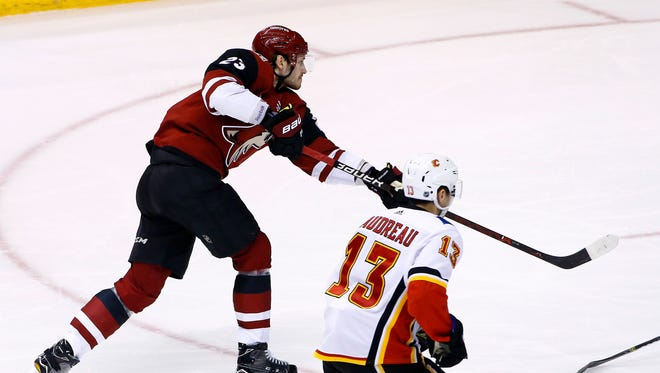 Arizona Coyotes defenseman Oliver Ekman-Larsson (23) scores a goal as Calgary Flames left wing Johnny Gaudreau (13) looks on during the third period of an NHL hockey game, Monday, March 19, 2018, in Glendale, Ariz. The Coyotes defeated the Flames 5-2.