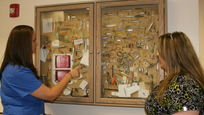 Phillippa Arnold (left), trauma program manager at Baxter Regional Medical Center (BRMC), and Angel Strain, trauma/stroke coordinator at BRMC, marvel at the variety of fishing lures on display in the center's emergency department. Dozens of patients have passed through emergency over the decades to have lures and hooks removed after accidentally getting snagged by an errant cast or inadvertently hooking themselves.