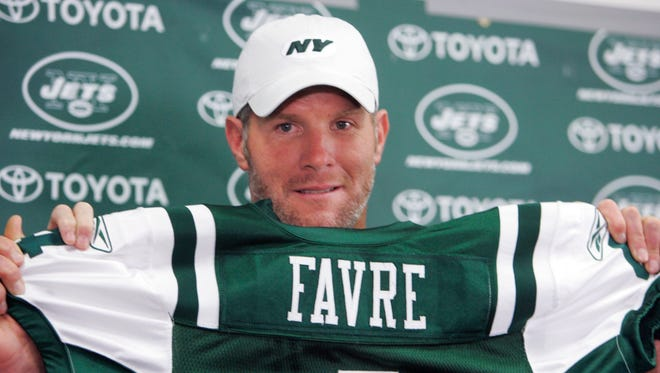 Brett Favre holds up his New York Jets jersey at Cleveland Browns Stadium before an NFL exhibition game Aug. 7, 2008, in Cleveland. Favre was traded from the Green Bay Packers to the Jets.