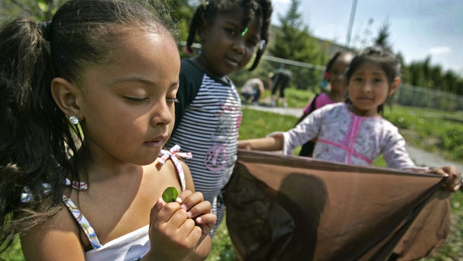 """""""I wish we could keep the earth clean,"""" wishes Alexis Faulkner (left) on a three-leaf clover she found while helping to clean up on Earth Day in 2010."""