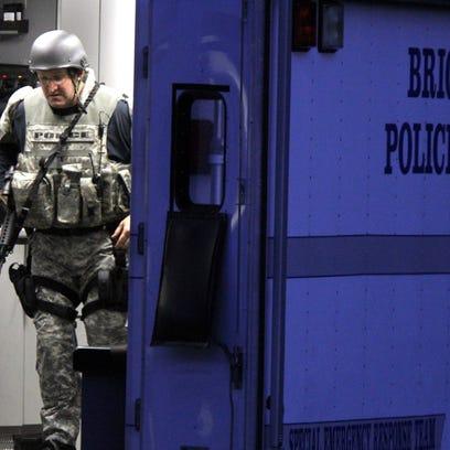 Swat team members gather on Millbrook Road in Brick