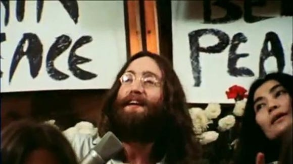 "John Lennon performs the song ""Give Peace a Chance"" in a Montreal hotel room"