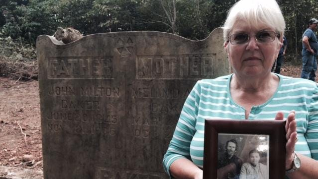 Earlene Cullen and other relatives hope to keep the grave sites of 10 ancestors undisturbed in a family cemetery in Avery's Creek. She's holding a picture of her great-grandparents buried beneath this headstone, John Milton and Melinda Baker.