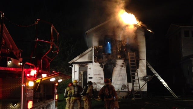 Firefighters work to extinguish flames Wednesday morning at home on Clay Street.