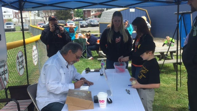 Former MLB pitcher Ross Grimsley signs an autograph for Littlestown youth baseball player Tyler Sheely on Saturday.