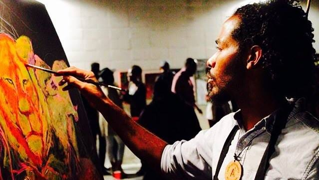 Artist Cory Williams as he works on a recently completed painting.