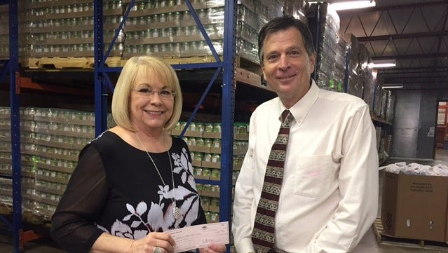 Jeff Eckard, president of Abilene Founders Lions Club, presents a Thanksgiving donation to Jody Houston, of the Food Bank of Abilene.