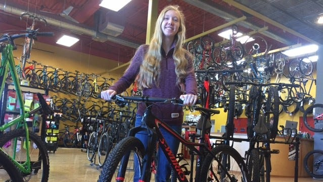 Lauren Lackman, 15, stands with her mountain bike at Rib Mountain Cycles. Her dad has owned the store for the last 20 years, and instilled a love for bikes in Lauren.