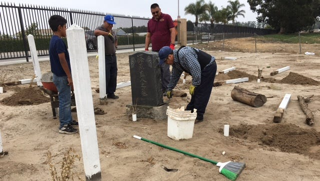 Armando Ruiz, right, steadies the headstone at the Japanese Cemetery in Oxnard as others watch. The cemetery was vandalized last month.