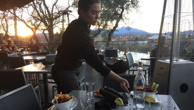"""Server Kenzie Moore and half-price """"mid day menu"""" appetizers at View 202 in Redding."""