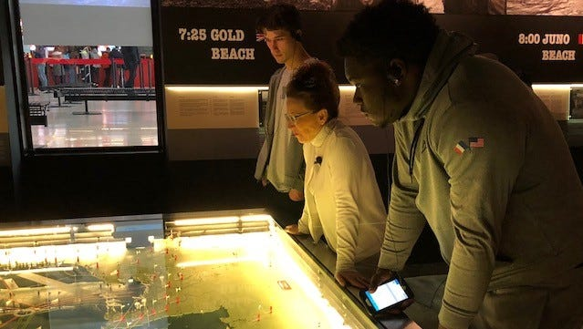 A couple Michigan players check out a map at the Caen-Normandie Memorial in France on Sunday.