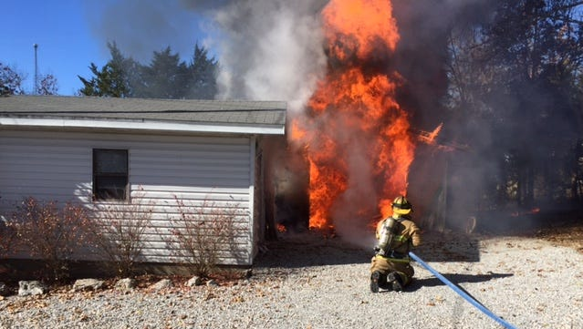 A Mountain Home firefighter battles a blaze at 30 Home Place on Tuesday morning.
