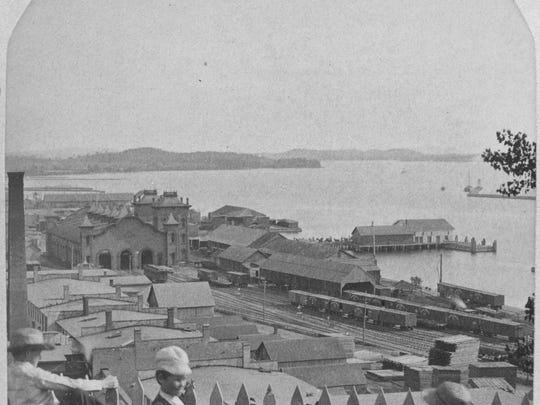 A view of Burlington's waterfront, looking southwest from Battery Park in the mid-19th century. Clockwise from upper right, the view includes the Breakwater, ferry and steamboat docks, railroad cars, piles of lumber, and the smokestack of the Pioneer Mechanics Shops where lumber processing took place.
