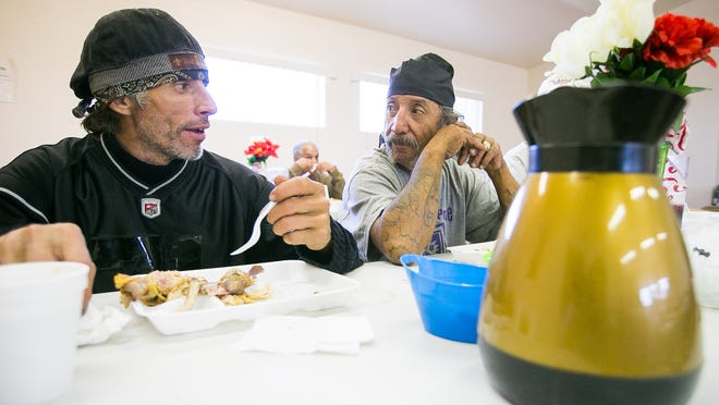Ernesto Vigil, left, and Louis Escobedo eat at the St. Vincent de Paul dining hall in El Mirage on Wednesday, January 21, 2015.