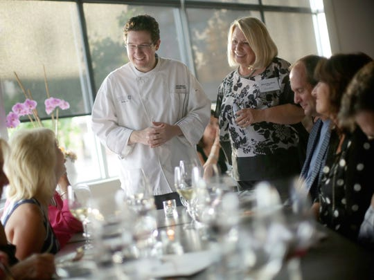 Bistro 82 chef Derik Watson, left, and Detroit Free Press Restaurant Critic Sylvia Rector chat with guests during the Detroit Free Press Top 10 Takeover dinner series at the Bistro 82 in Royal Oak on Monday, August 10, 2015.