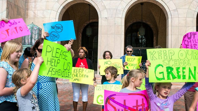 Parents, teachers and students from Isaac Dickson Elementary School hold colorful signs and chant outside the Asheville City Building to protest a potential Duke Energy substation going in next door to the school.